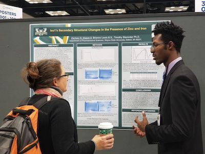 Wayne State student Zachary Mason, right, presents his research at the ABRCMS in 2018.